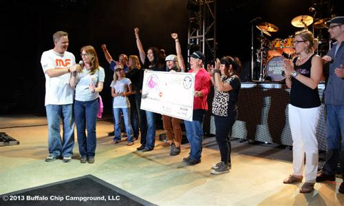 Chris McGee (MC) and Toni Woodruff (Sturgis Buffalo Chip) sharing the microphone.  Holding the check is Laura Klock (Helping With Horsepower), Jessi Combs (All Girls Garage) and Christine Paige-Diers (The Sturgis Motorcycle Museum)
