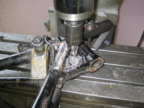 Here you see the frame in my milling machine so I can remove the cast in steering lock boss from the neck area.