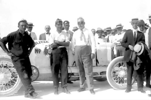 Teddy Teztlaff (with arms folded) standing next to Governor William Spry (with goggles) after the 142.857 mph run. Leaning on the right rear tire is the riding mechanic of the Blitzen Benz II, Do- menich Basso. The individual wearing goggles between Tetzlaff and Spry may be Salt Lake City Mayor Samuel C. Park.