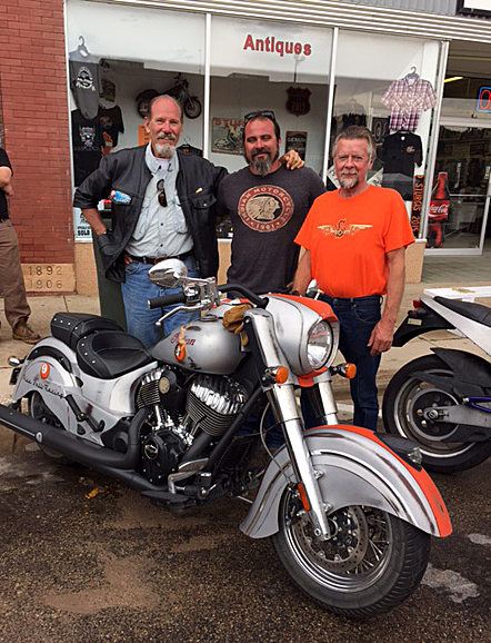 The old guy and young rider who rode my Indian from Charleston, SC to Sturgis, and Arlin Fatland in front of his store celebrating 45 years on Main.