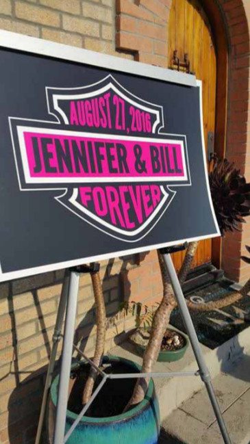 A Harley-themed wedding logo sign welcomed an eclectic mix of guests to Keith Ball's Intergalactic Headquarters for the wedding of Jennifer Thomas to Biker Author Bill Hayes.
