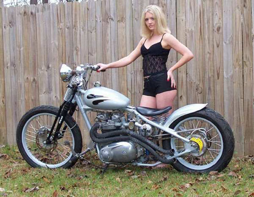 blonde in black standing silver bike